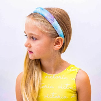 another child model in a blue and purple headband