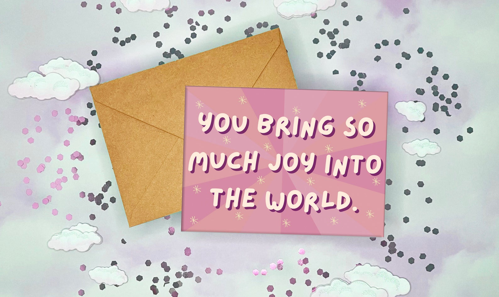 pink greeting card with yellow stars and white bubble text that reads you bring so much joy into the world
