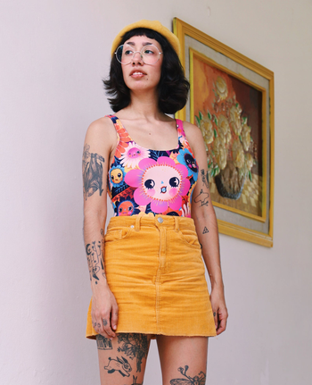 the owner of the etsy shop wearing the bathing suit as a bodysuit with a skirt