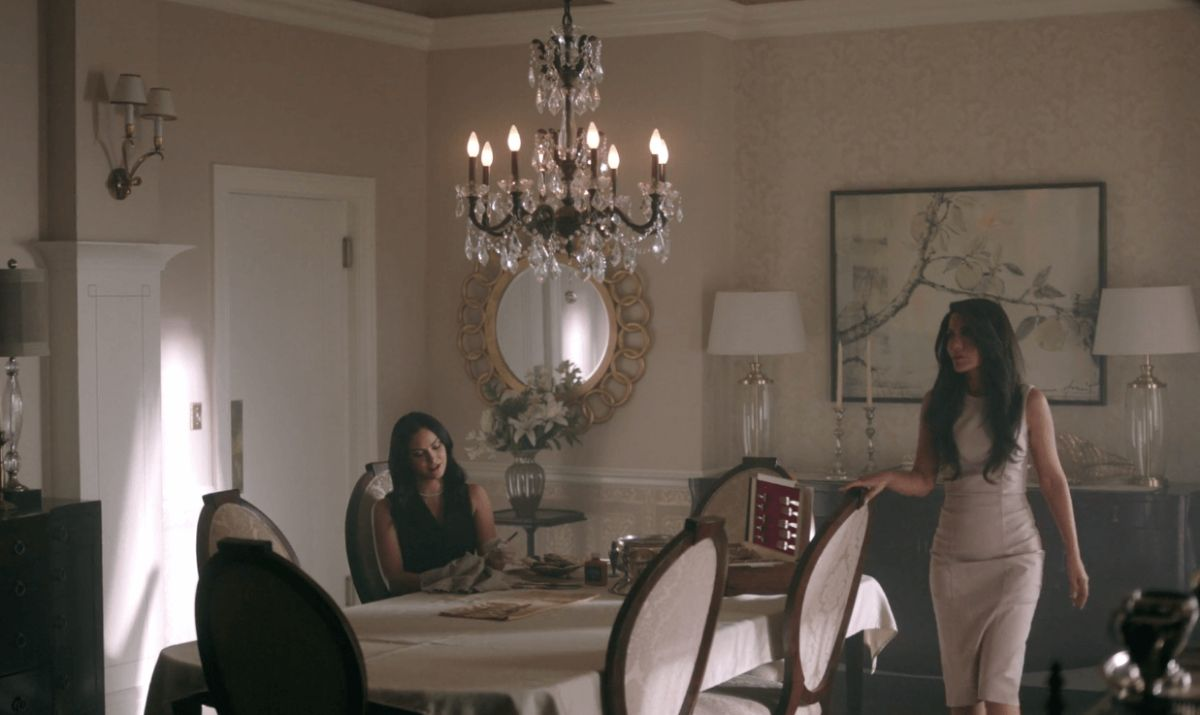 two women in tight dresses and long hair sit in a dining room with a large chandelier