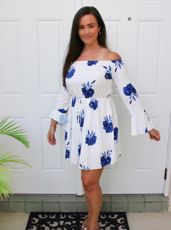 reviewer wearing white and blue dress