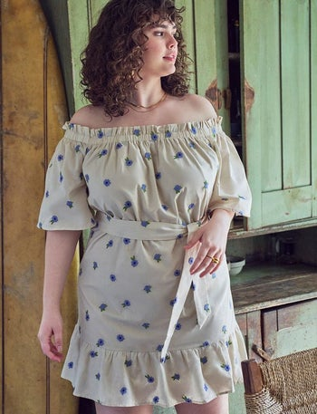 model in white mini with elbow sleeves, tie waist, and periwinkle flowers