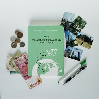 green book surrounded by photos and international money