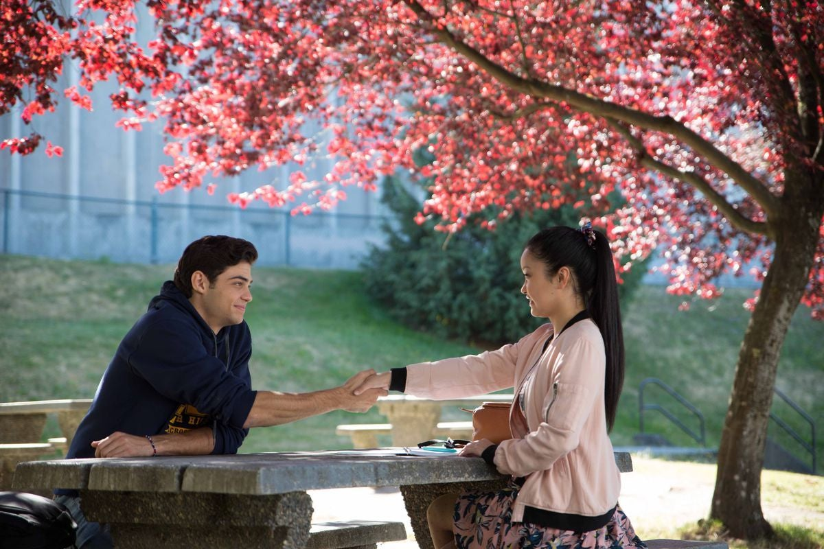 Lara Jean and Peter holding hands at a picnic table