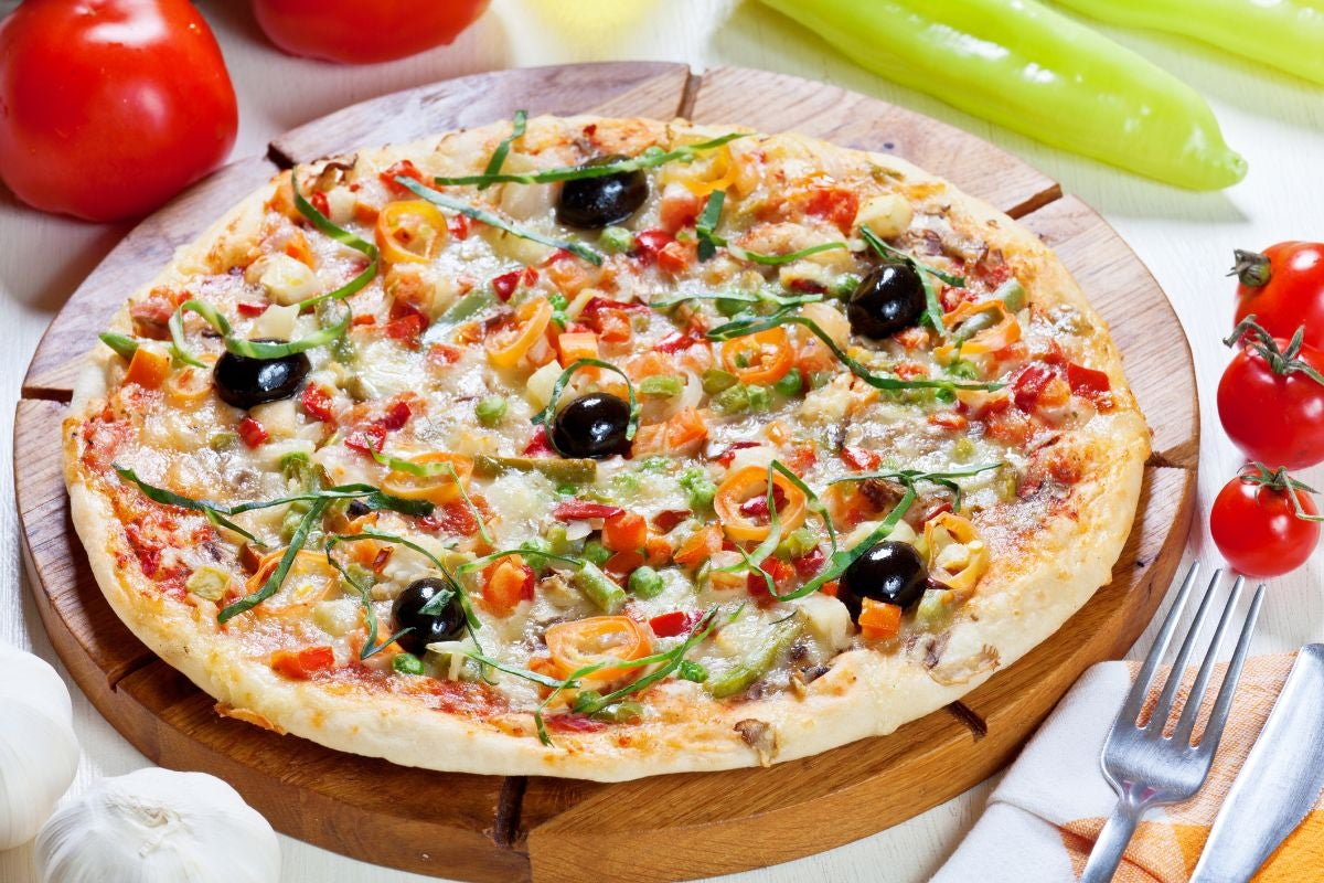 Pizza topped with olives, tomatoes, and green peppers