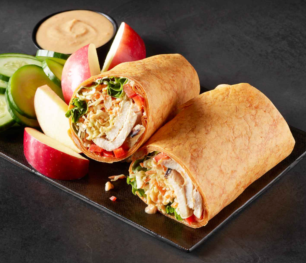 A wrap made with grilled chicken, peanut sauce, and chili lime sauce with apple slices on the side