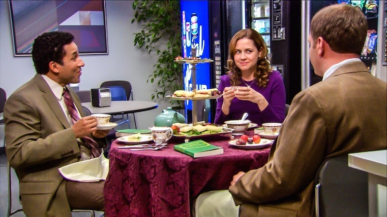 The Finer Things Club is sitting at a table eating food from a tray