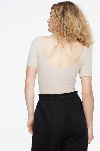 back view of the same model in a tan bodysuit