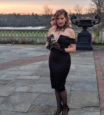 a reviewer in a black dress with off the shoulder styling