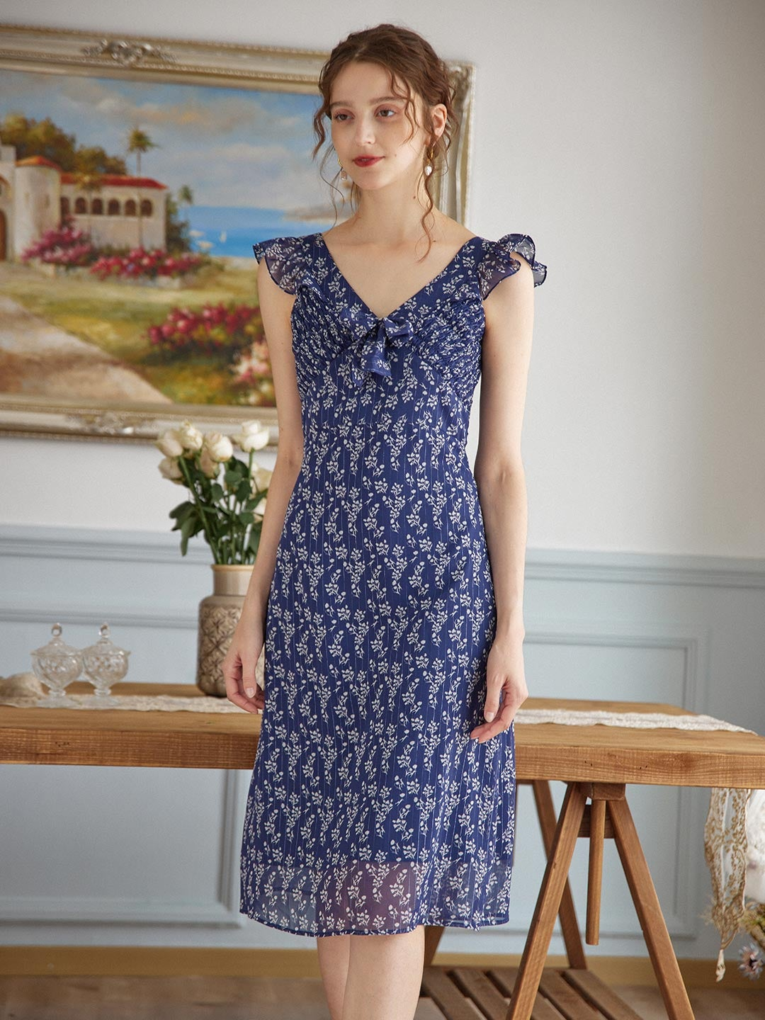 model wearing the v-neck ruffle sleeve dress in navy blue with white flowers all over it