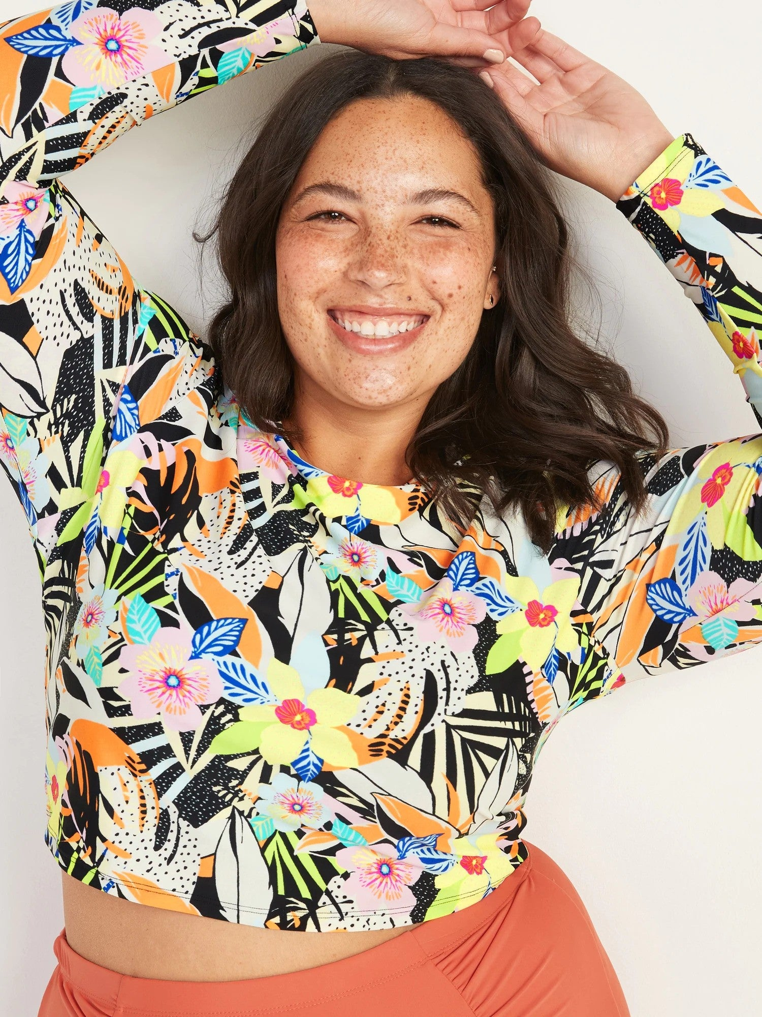 model wearing top with illustrated monstera leaves, hibiscus flowers, palm leaves, and orchid flowers in black, orange, pink, blue, yellow