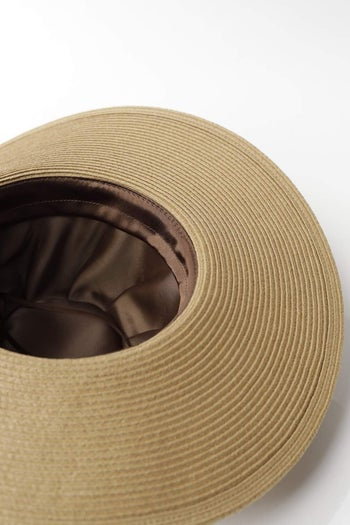 the wide-brim floppy hat in tan straw, with a thin dark brown cord