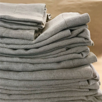 A pile of folded light grey linen