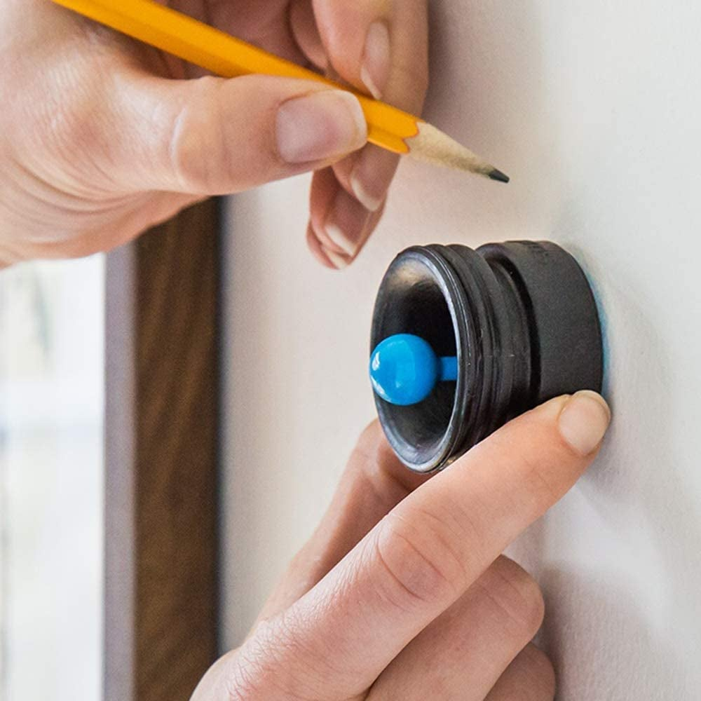 hand using the small round tool with blue knob against a wall