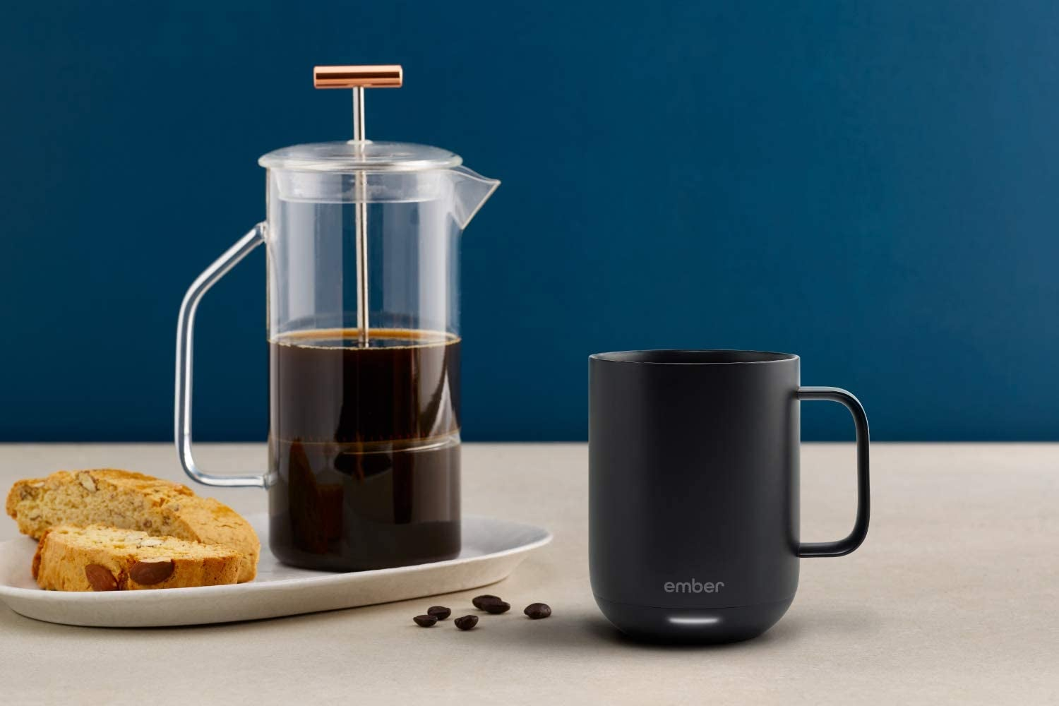 The black mug on a table next to a french press and biscotti