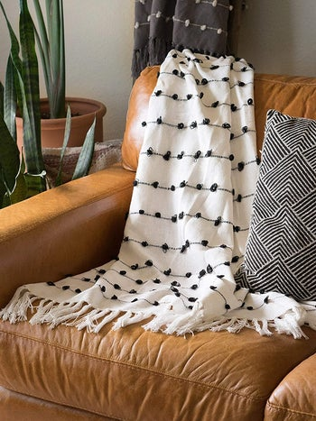 the white throw blanket on a couch
