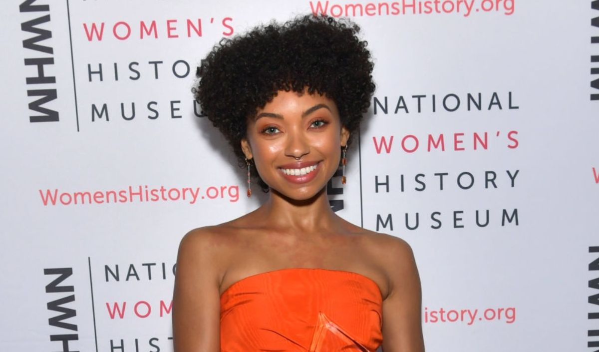 A woman with an afro is smiling. She wears a strapless dress