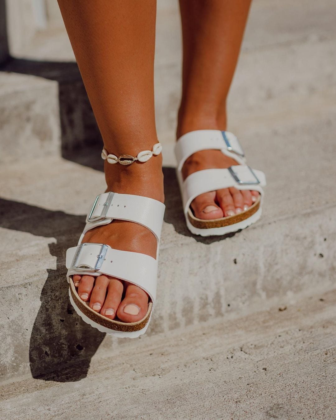 a model in white birkenstock sandals at the beach