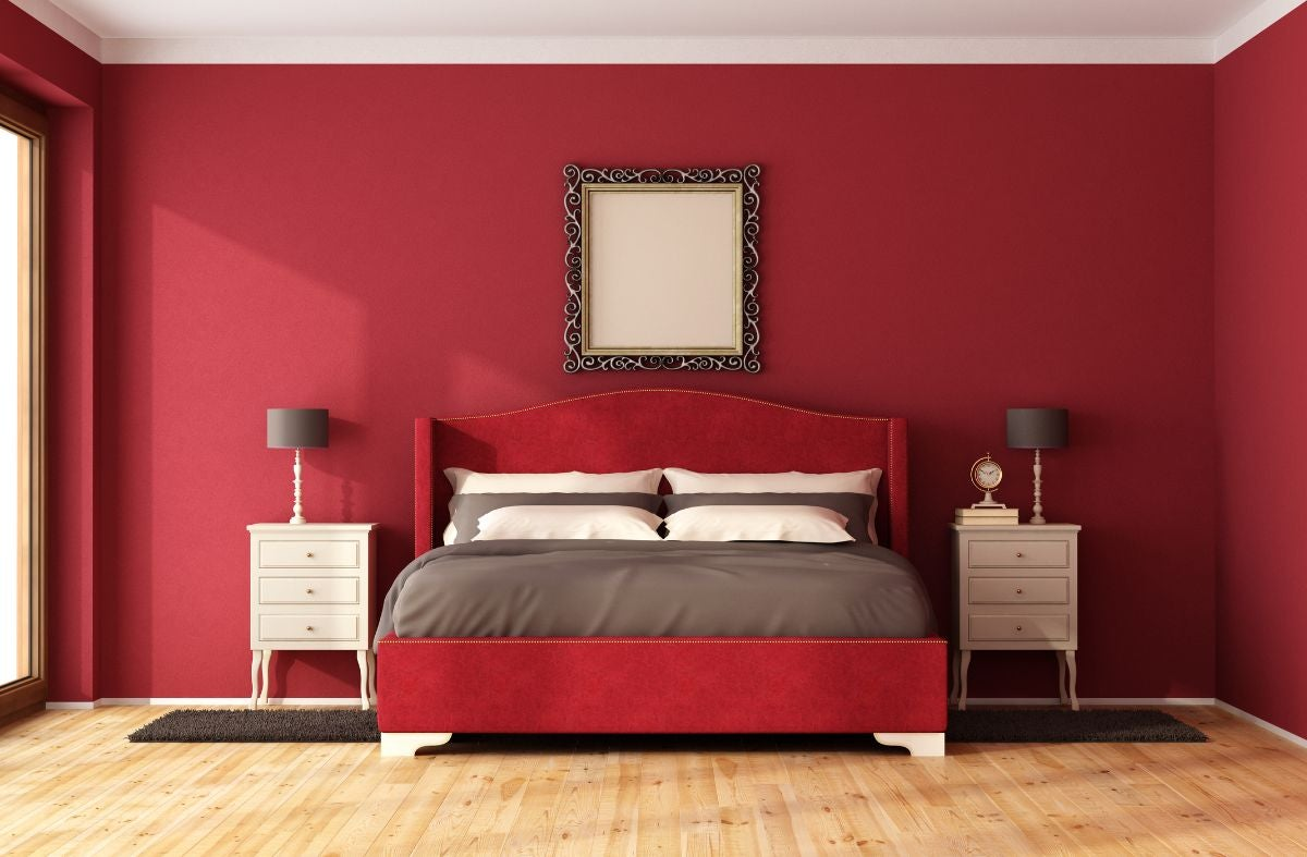 A simple bedroom with a bed and two dressers surrounding the bed, plus a wooden floor and a mirror above the bed