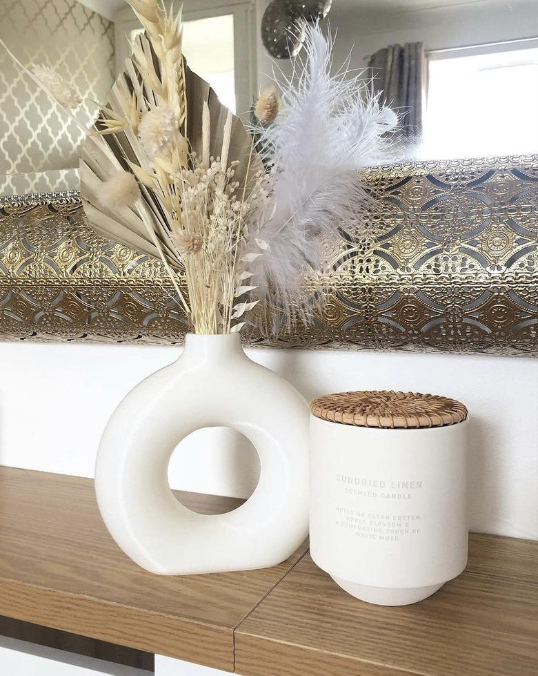 the white nordic donut vase next to a candle
