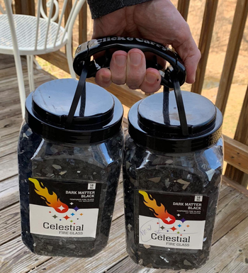 a reviewer photo of a hand holding two ten-pound jars of fire glass using the bag holder