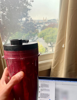 a reviewer photo of them holding a blended smoothie inside of one of the to go cups the blender comes with while studying on a laptop