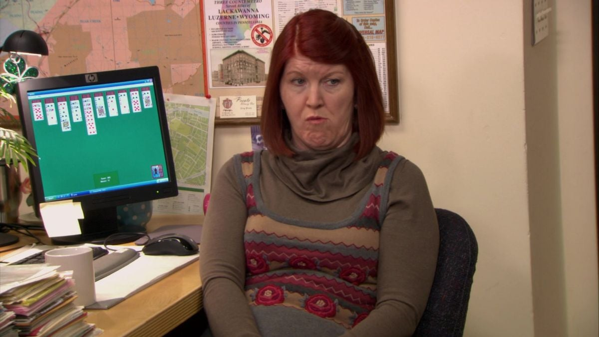 "Meredith Palmer is sitting at a computer desk with ""Solitaire"" on her screen"