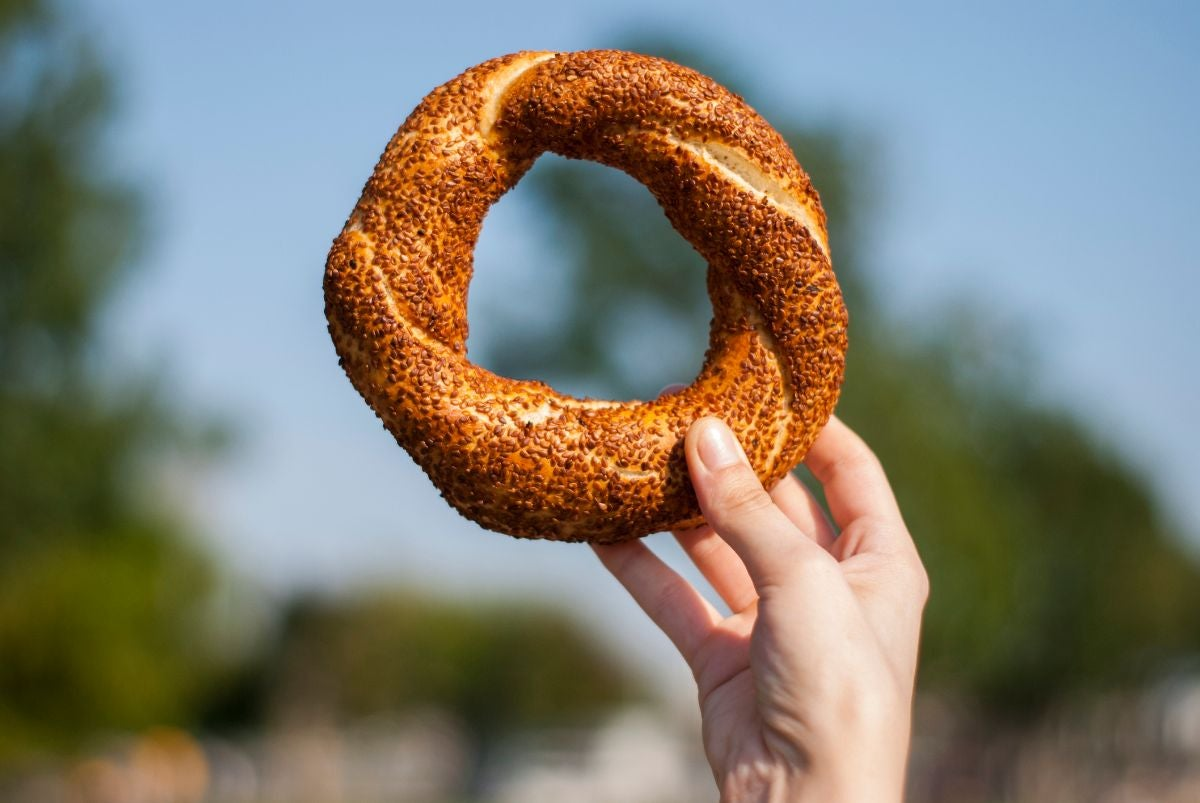 A circular bread with a hole in the middle covered in poppy seeds