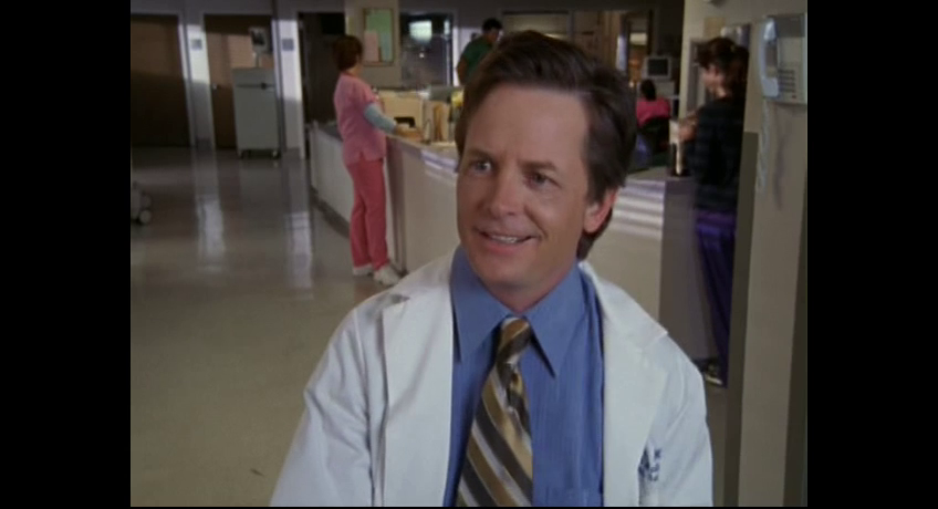 a middle aged doctor smiles slightly in a hospital