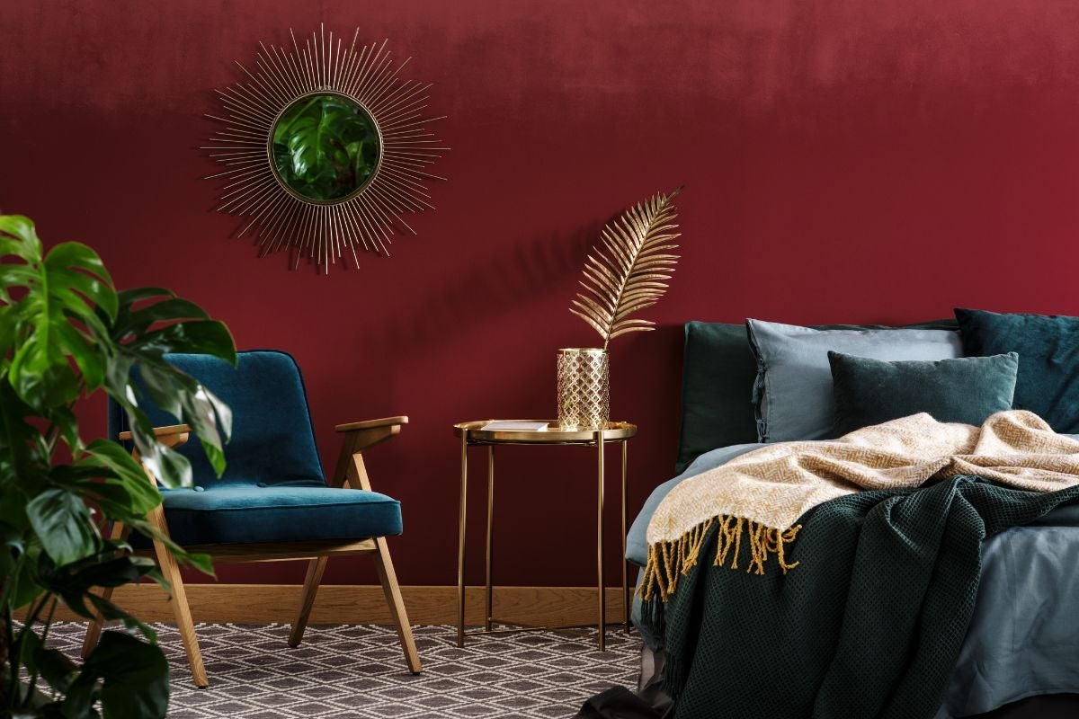 A dark bedroom with a fake golden plant, bed, and tile floor