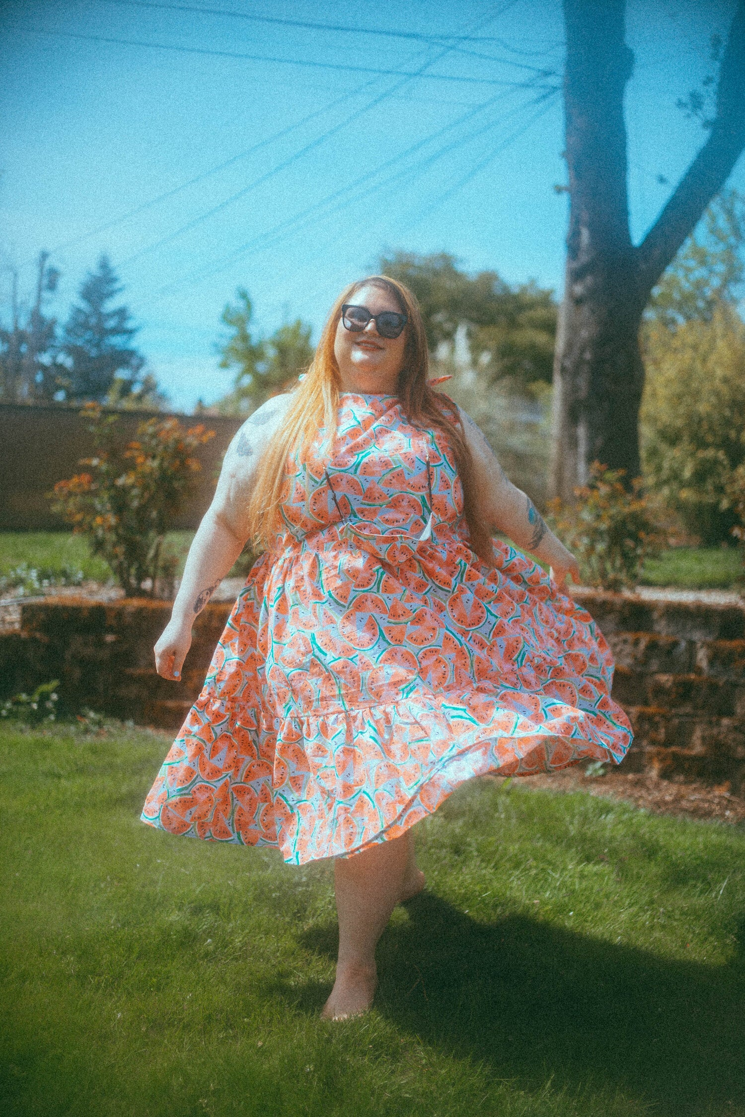 Plus-size model waring a light blue midi dress with watermelons on it