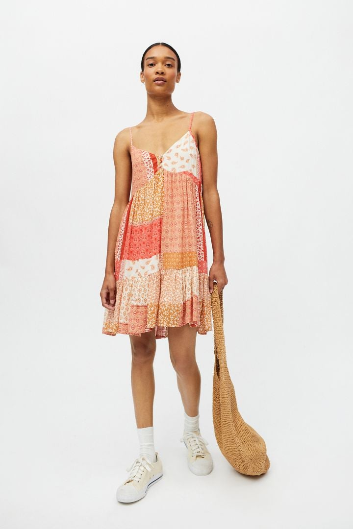 model wearing the tiered printed dress in different colors of orange