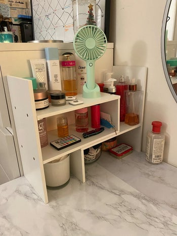 Reviewer photo the white shelves on a marble countertop with beauty products on it