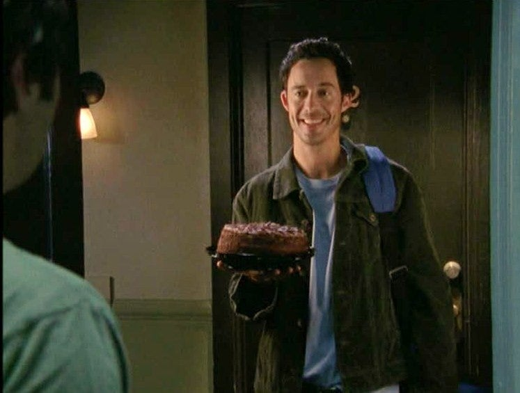 a man wearing a corduroy jacket is smiling holding a cake