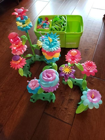 Reviewer's photo of plastic flower toys and bucket