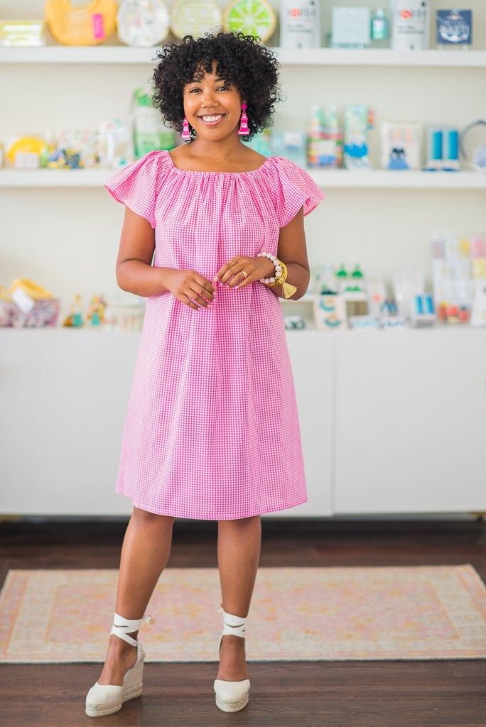 business owner waring the knee-length pink gingham dress with short sleeves on the shoulder