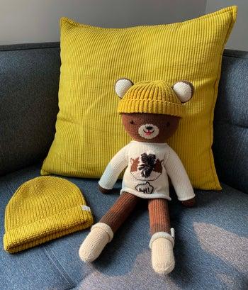 Stuffed brown bear wearing yellow beanie next to child's yellow beanie