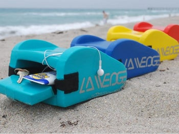 three wedge pillows on the beach with the storage compartment open holding a bottle of sunscreen, headphones, and keys