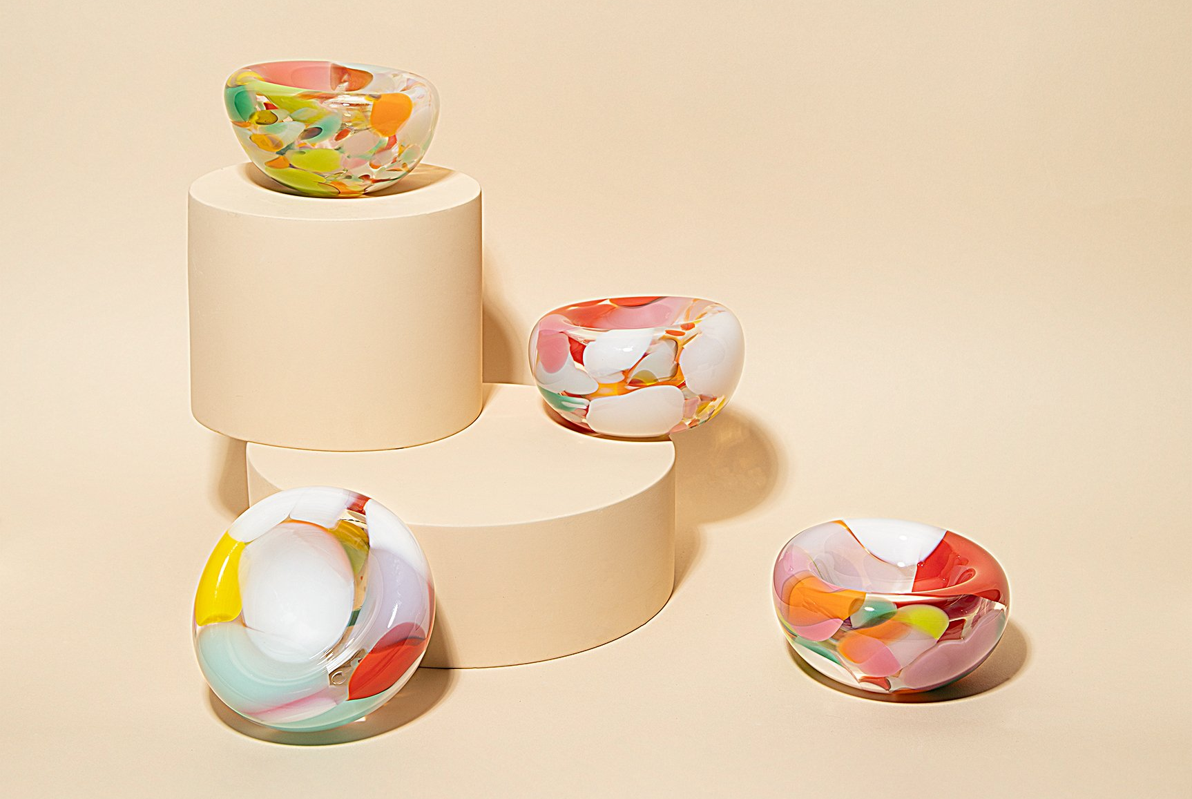 four glass ashtrays with different color splotches on them