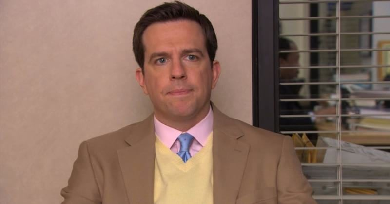 Andy Bernard is sitting a chair with blinds behind him