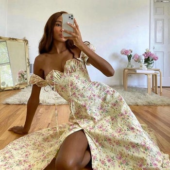 model taking a selfie while wearing the dress in apricot with pink flowers