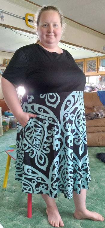 reviewer wearing the dress with a black bodice and black and teal skirt