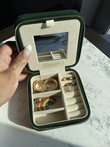 a reviewer's green velvet case holding two sets of earrings and three rings