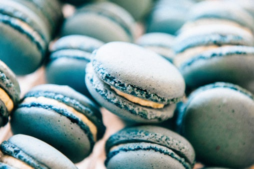 Blue macarons are piled on top of each other in a carton