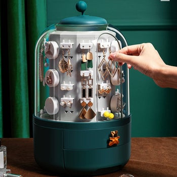 hang takes out danglng earrings from clear pod with green drawers with teddy bear pull