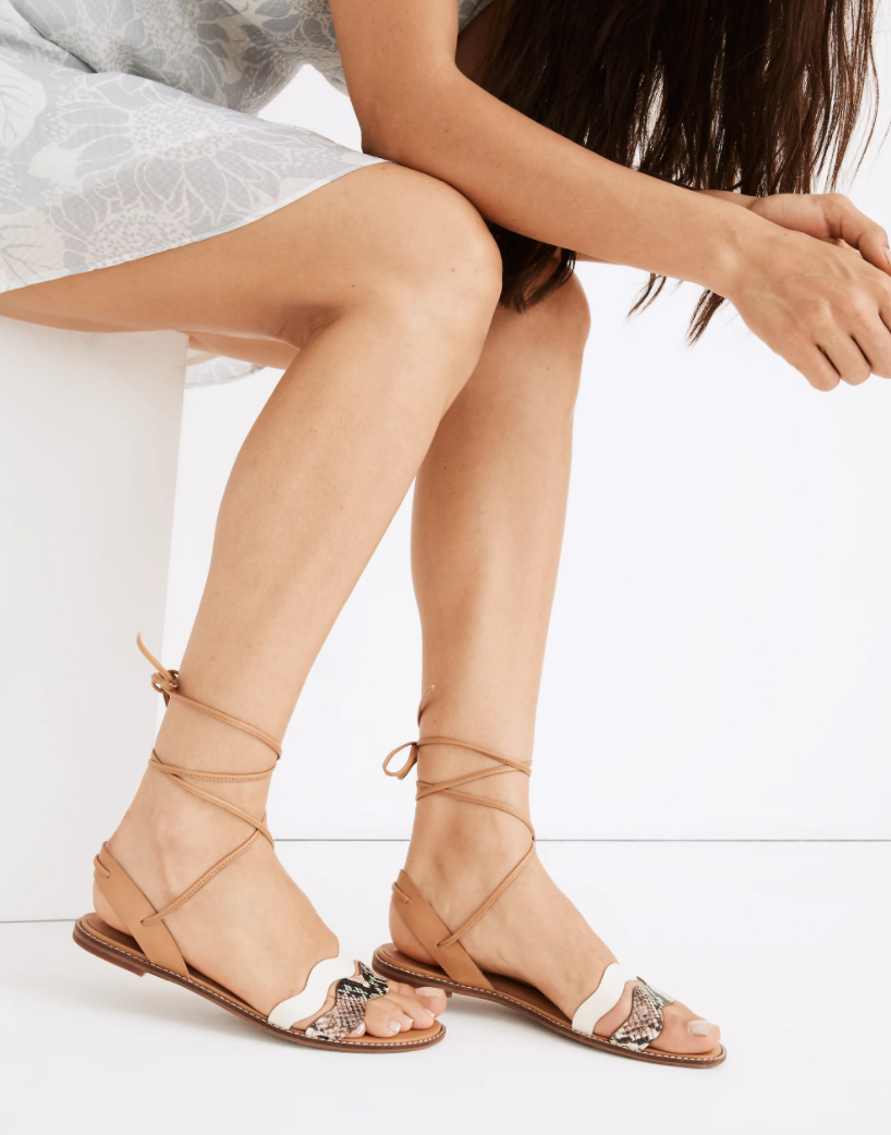 a model wearing tan lace-up sandals with two wavy bands across the top of the foot; one in white and one in snake print