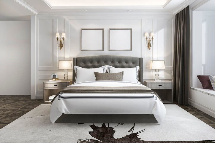 A bedroom with a large bed with a plush headboard in the middle of the room, two nightstands on either side of the bed, and a large bay window off to the side with pillows on top of it