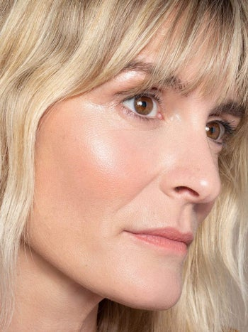 blonde model wearing a gold-tinted highlighter over coral blush