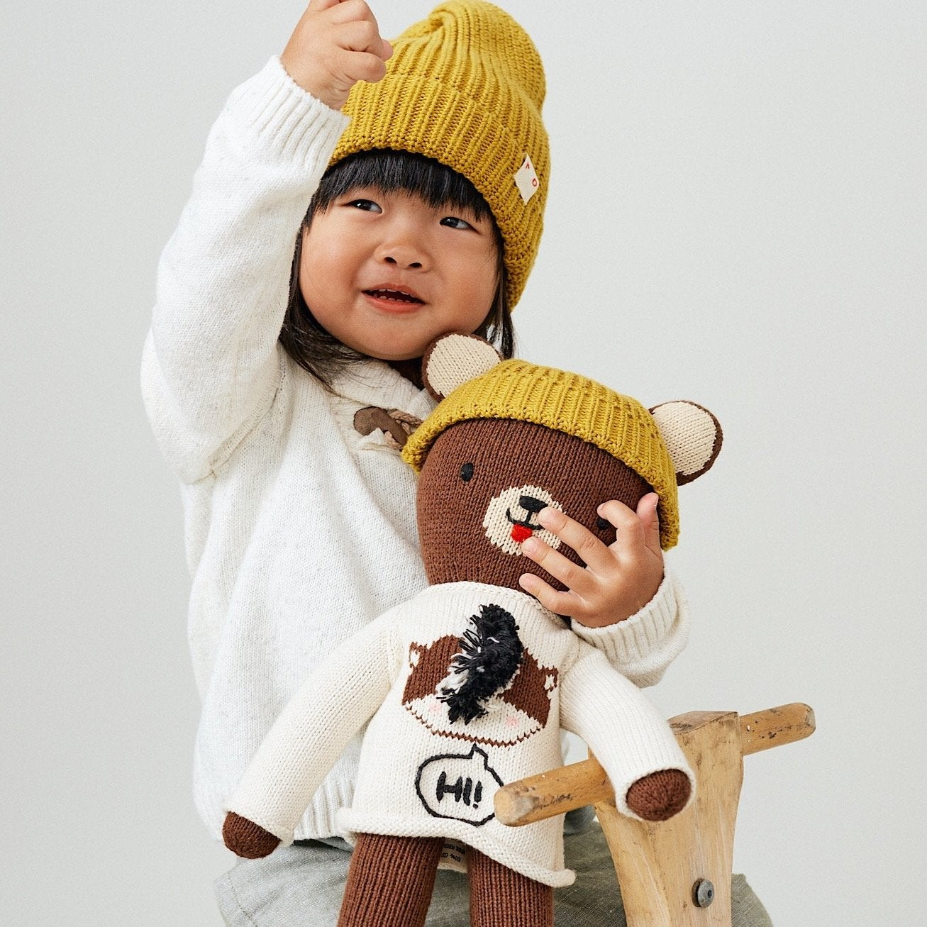 Child model with stuffed brown bear wearing yellow beanie