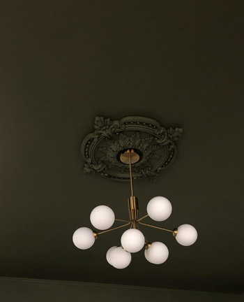 reviewer image of medallion installed and painted dark green to match the rest of ceiling